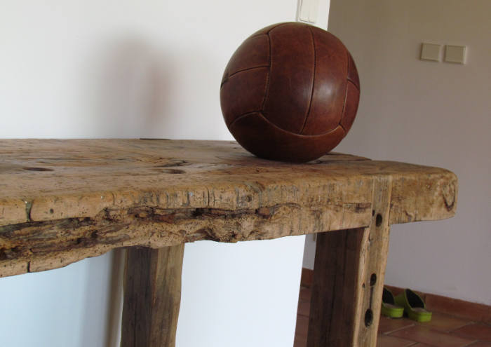 Old leather volleyball on wooden furniture
