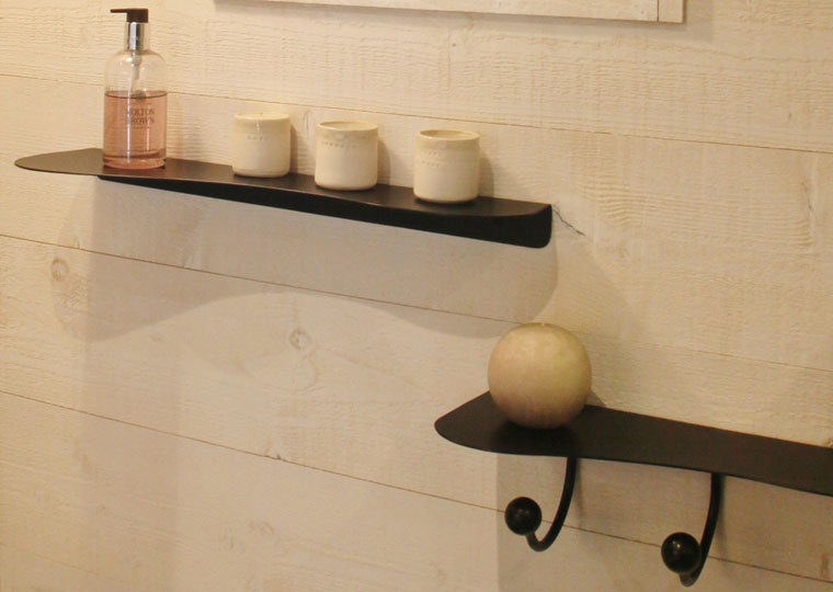 Close-up on black metal wall shelves in organic shape